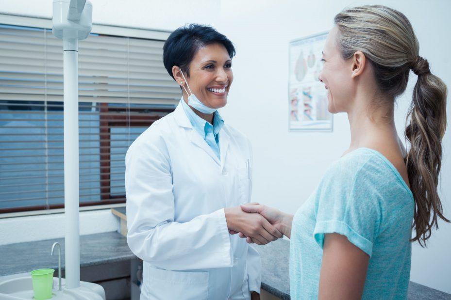 Dentista cumprimentando a sua paciente fiel, resultado de marketing na odontologia bem feito