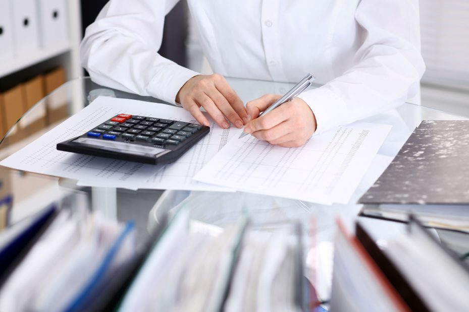 Dentista fazendo gestão odontologia calculando seu faturamento na calculadora