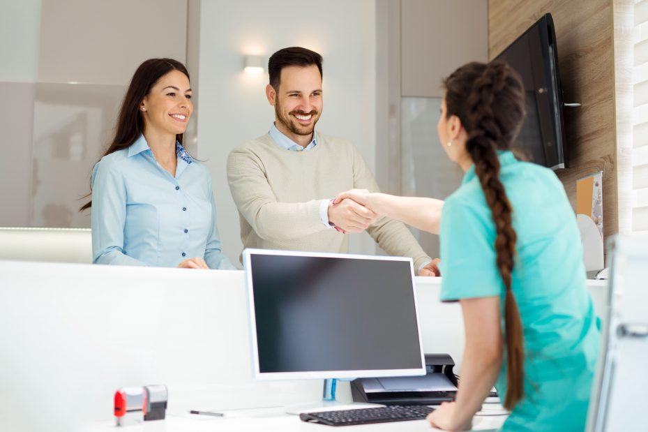 Dentista cumprimentando paciente e seu programa para consultório odontológico aberto no computador