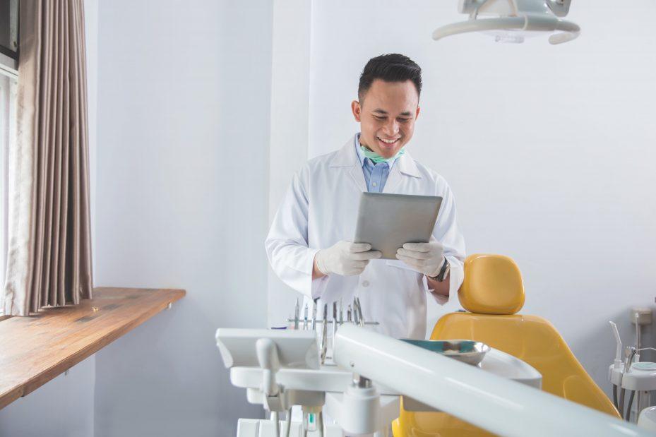 Dentista vendo seu programa para consultório odontológico no tablet