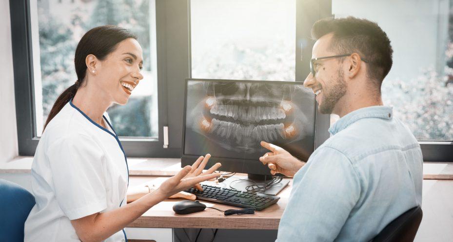 dentista conversando com paciente em frente ao computador com programa para clínica odontológica