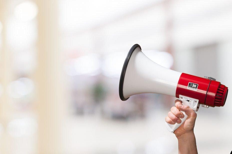 Mulher segurando megafone representando propaganda para consultório odontológico