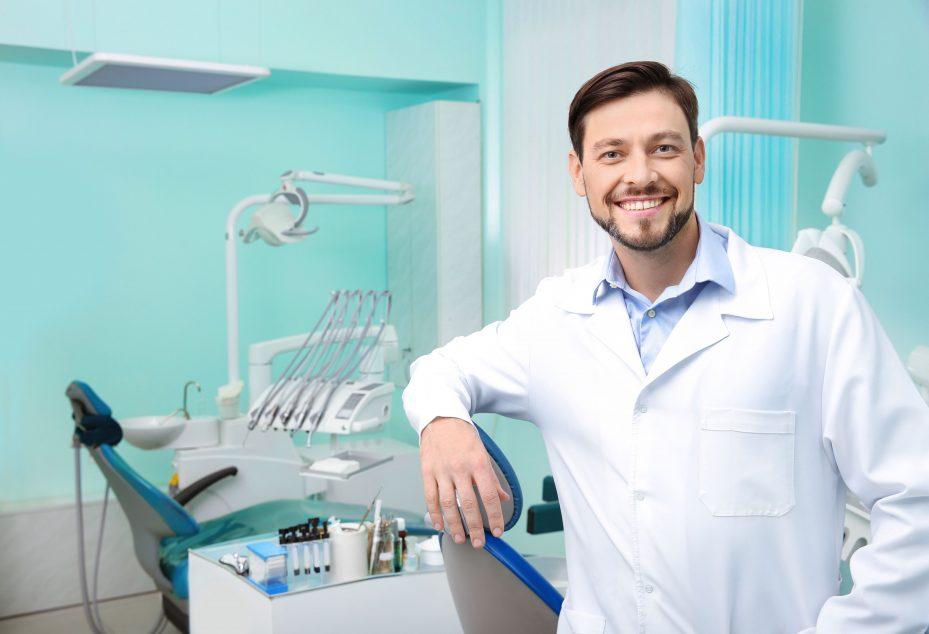 Dentista sorrindo na sua clínica que conta com um sistema para clínica odontológica