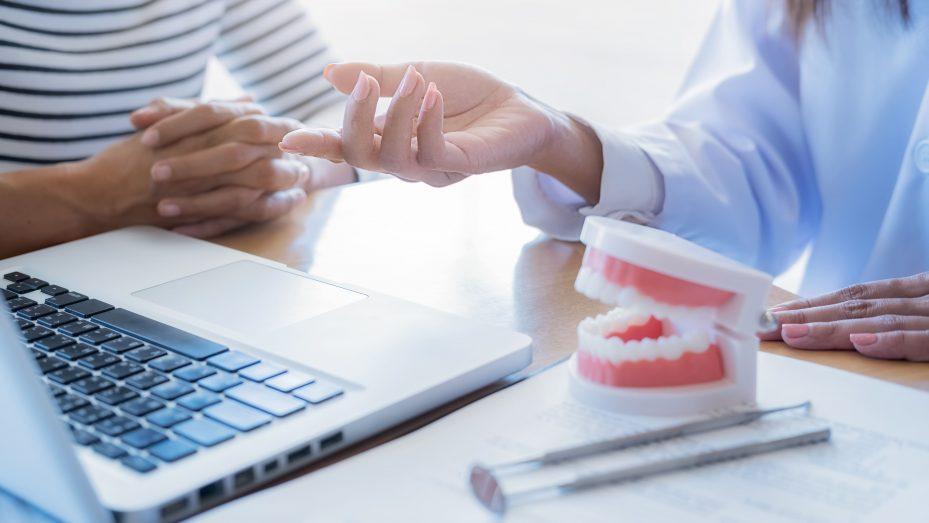 Dentista, paciente e notebook com um sistema para clínica odontológica