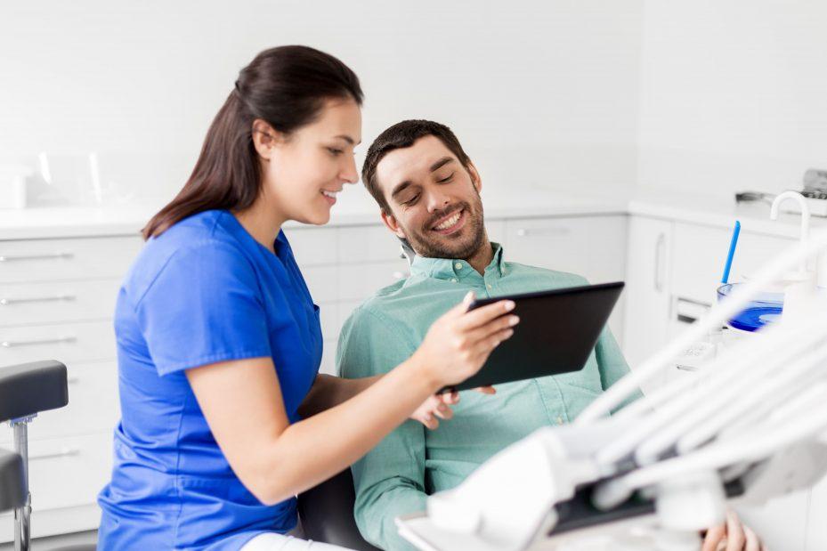 Dentista mostrando ao paciente seu software odontológico pelo tablete