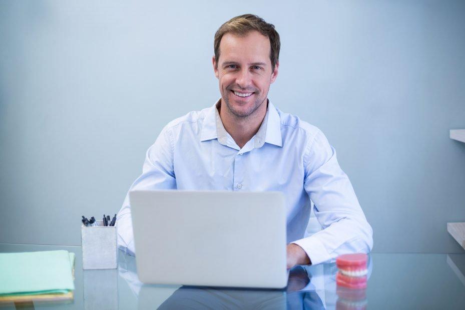Dentista com notebook vendo seu software odontológico