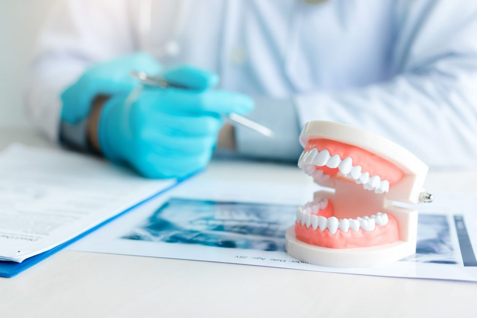 Dentista sentado fazendo anotações em seu prontuário odontológico
