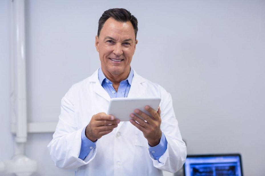 Dentista segurando o tablet com seu sistema odontológico