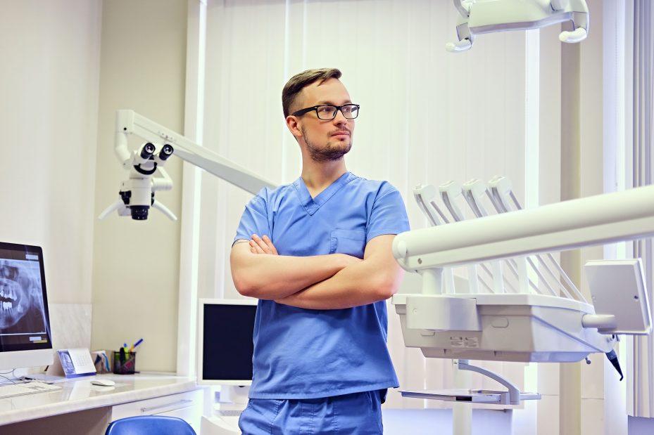 Dentista de pé em frente ao seu software para dentistas