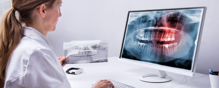 Uma dentista acessando seu software para dentistas no computador