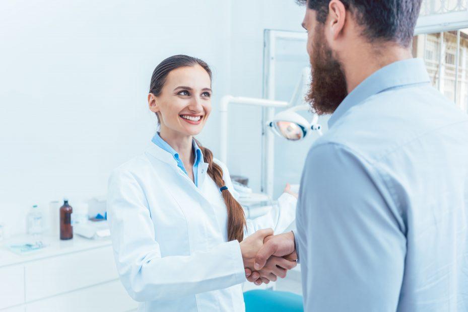 Dentista cumprimentando o seu paciente com aperto de mão