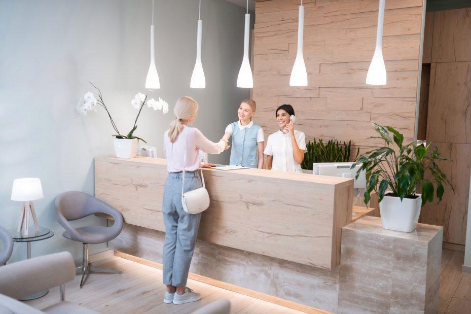 Dentista atendendo paciente com a decoração de consultório odontológico em destaque