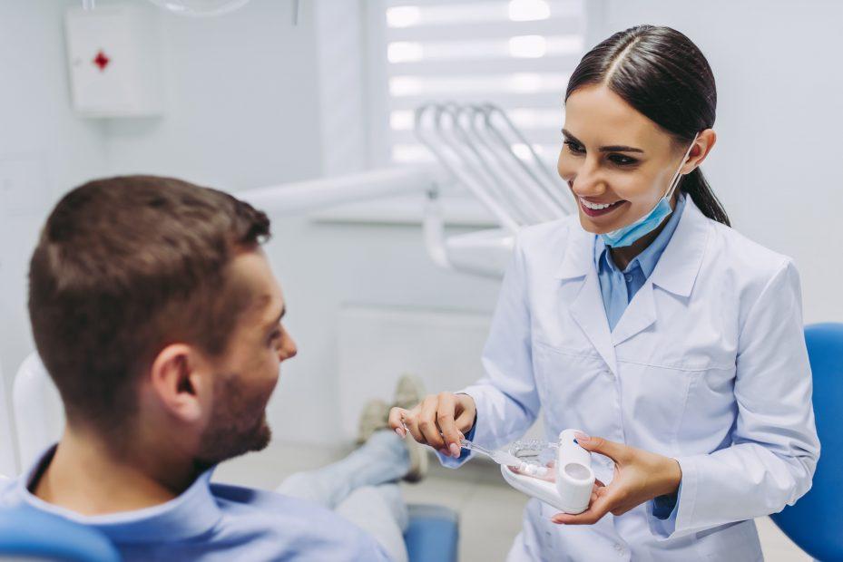 Dentista prestando atendimento humanizado ao seu paciente