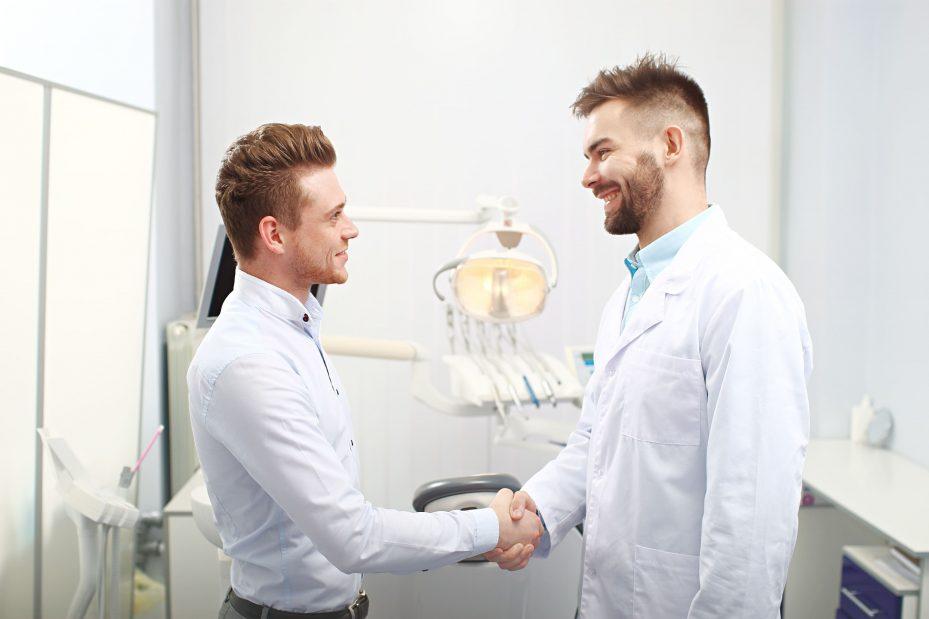 Dentista apertando mão de paciente