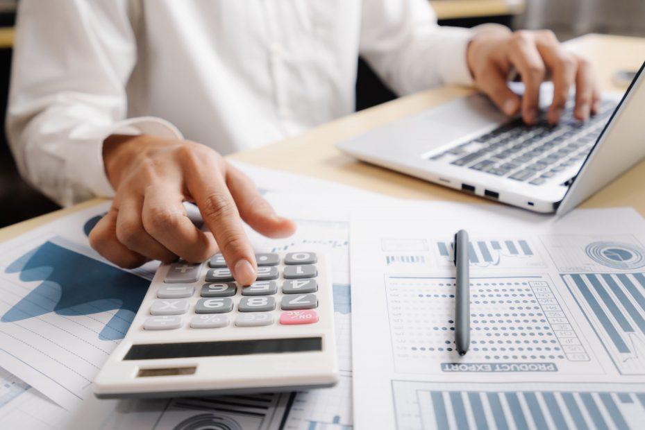 Dentista fazendo controle financeiro empresarial com calculadora