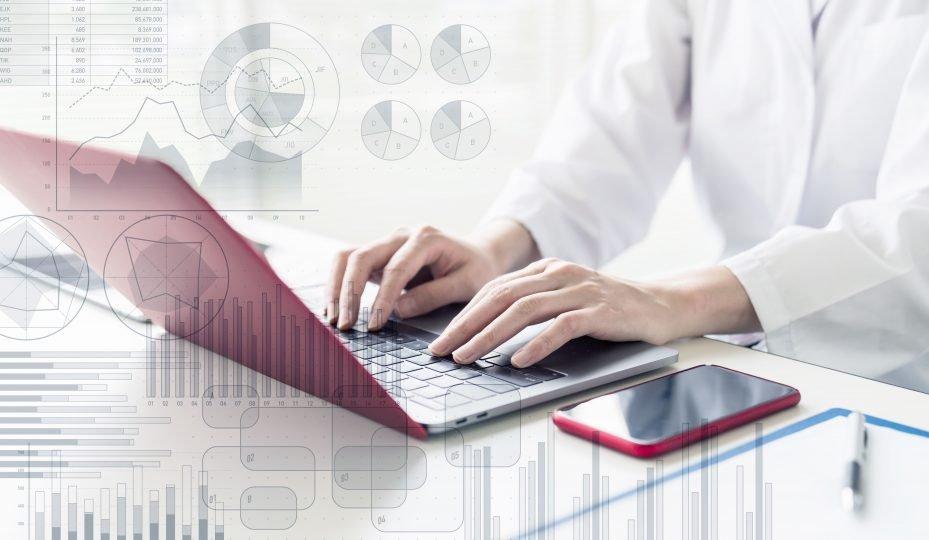 Dentista com seu computador fazendo controle financeiro para consultório