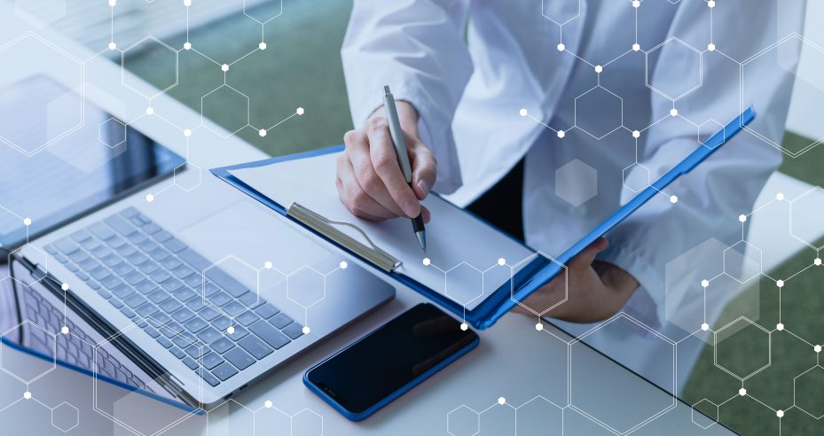 Dentista sentado à mesa com seu notebook para gerir empresa