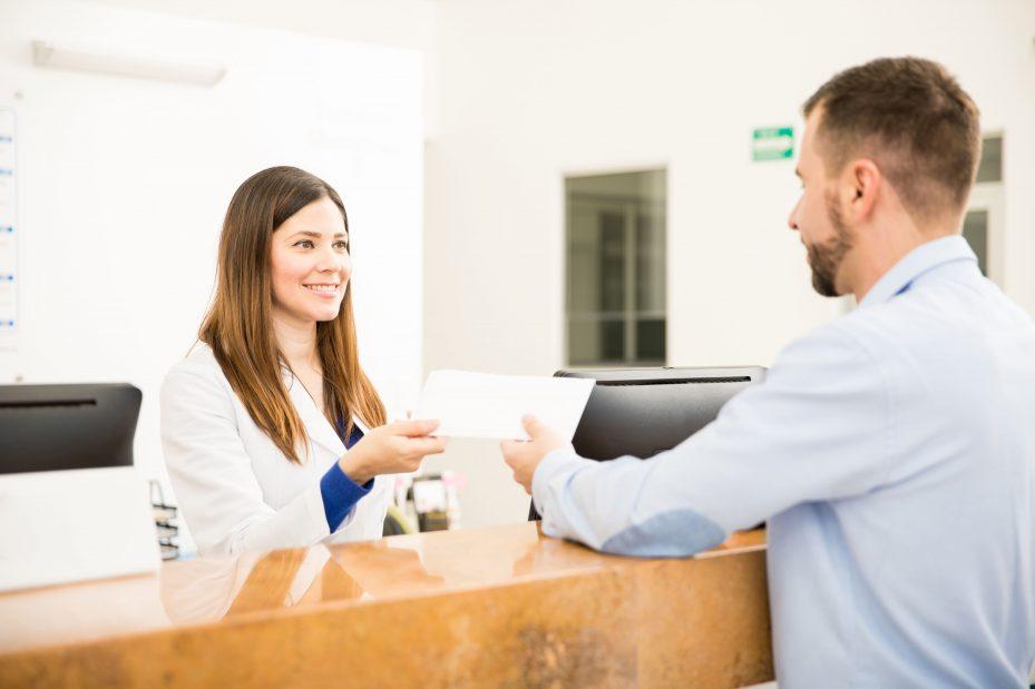 Recepcionista de clínica atendendo paciente