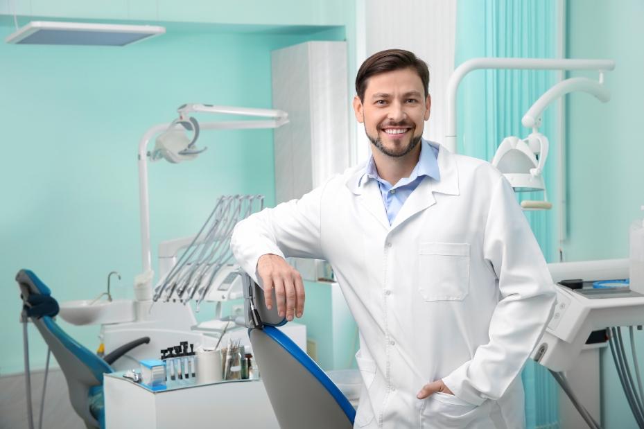 dentista sorrindo em seu consultório odontológico