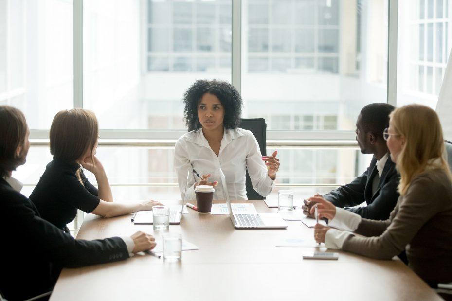 Mulher especialista em gerir uma empresa sentada à mesa com sua equipe