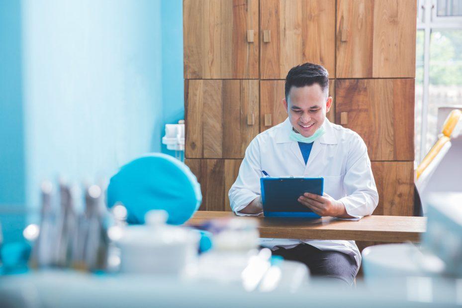 Dentista sentado fazendo a gestão de consultório odontológico
