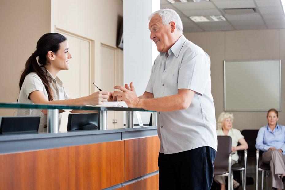 Secretária atendendo paciente idoso